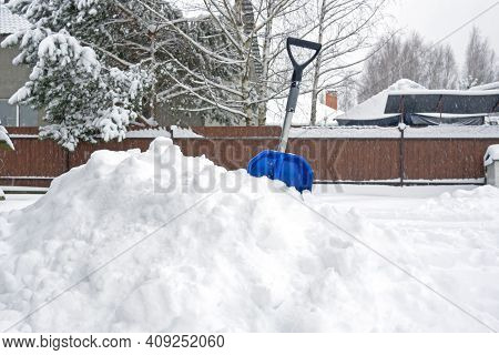Working Shovel In A Large Snowdrift After Clearing The Road