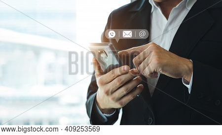 Hand Of Businessman Holding Mobile Smartphone. Contact Us, Customer Support Concept. Copy Space.