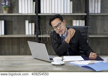 A Businessman In A Suit Grabs The Shoulder With His Hands. To Alleviate Pain From Prolonged Computer