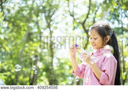 Adorable Happy Cute Girl Playful Foam Bubbles In Green Playground In Summer Outdoors. Funny Cheerful