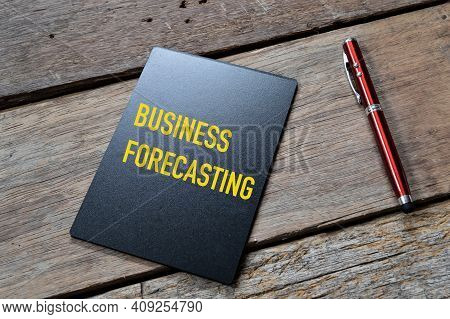 Top Angle View Of Pen And Blackboard Written With Business Forecasting.