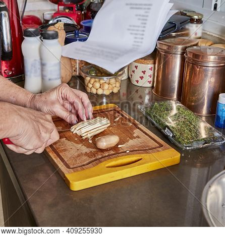 Woman Prepares Recipe At Home In The Kitchen. Cuts Mushrooms On Wooden Cutting Board