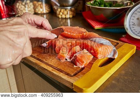 Cooking At Home In The Kitchen According To Recipe From The Internet. Woman Cuts Fresh Salmon With K