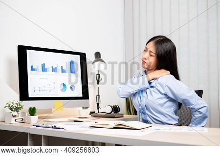 Asian Female Accountant Is Tired From Working In A Chair, Stretching To Relax And Relax While Workin