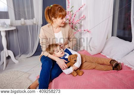 Young Mother Holding Her Little Sick Boy. Sick Child With High Fever Laying In Bed. Mommy Checking O