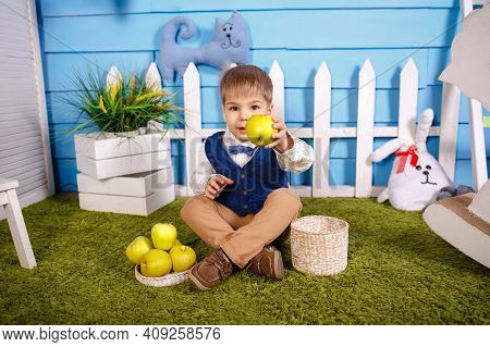 Child Eats A Ripe Sweet Apple. Boy Eating Healthy Food. Happy Caucasian Child Eating And Biting A Gr