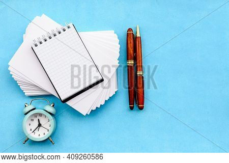 A Stationery Layout On A Blue Background - A Stack Of Blank White Cards, Parkers, And An Alarm Clock