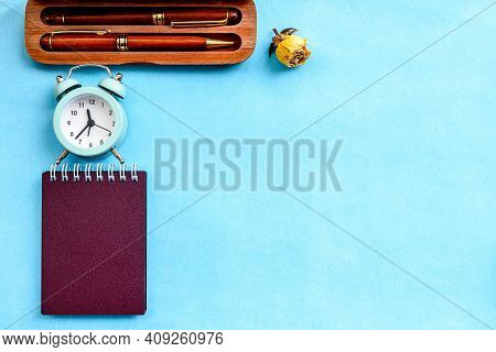 Stationery Layout On A Blue Background - A Notebook On A Spring, Parkers And A Vintage Alarm Clock.