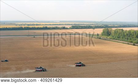 The Combine Harvester Mows The Crop Close To The Road, The Dust Is Raised From Behind The Machine In