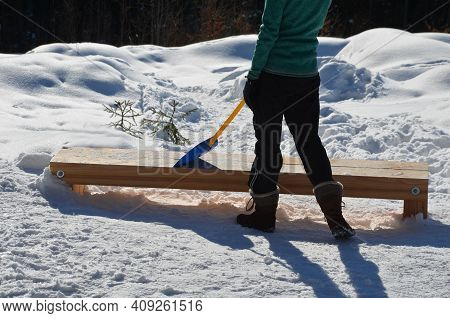 Woman, Girl With A Plastic Baby Shovel Cleans Snow From A Wooden Bench. He Has Winter Clothes And A