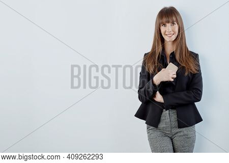 Business portrait of woman - happy young white businesswoman in business casual standing against gray wall. Copy space for text.