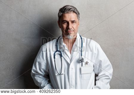 Portrait of trustworthy older confident doctor with gray hair wearing white lab coat standing against gray wall, smiling. Copy space.