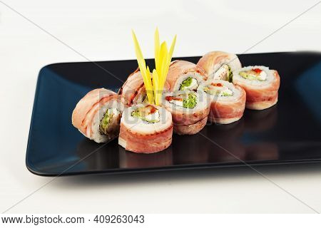 Sushi Roll With Bacon And Fried Sea Bass On A Black Plate, Ingredients Fried Sea Bass, Cream Cheese,
