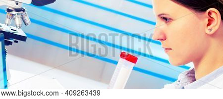 Portrait of pretty girl laboratory assistant analyzing a blood sample at hospital laboratory with laptop  pc