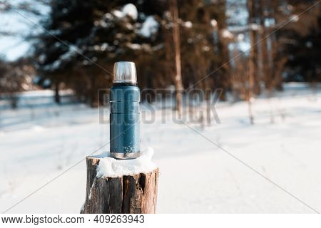 Thermos Standing On A Snowy Stump In A Winter Forest On A Sunny Day. Trekking Concept, Camping