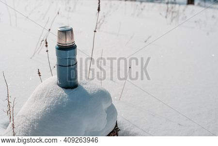 Blue Camp Thermos Standing In A Snowdrift. Winter Hike Concept.