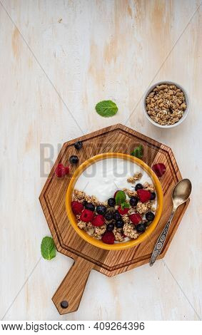 Breakfast, Unsweetened Yogurt With Baked Granola, Raspberries And Blueberries In A Yellow Bowl On A