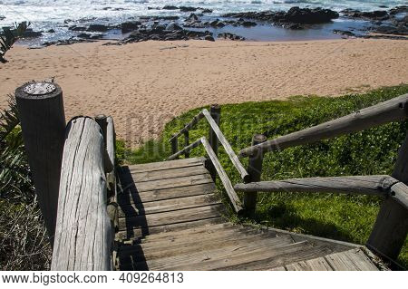 Wooden Steps Leading Onto Beach With Sean And Rocks Beyond