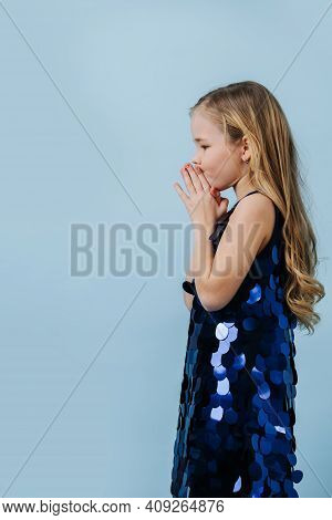 Cute Thoughtful Girl In A Glittering Blue Scaled Dress Pinching Her Mouth