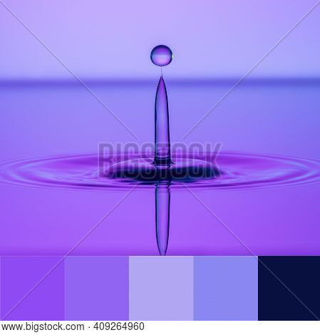 Water Droplets Almost Colliding So That One Droplet Is Finely Balanced On The Sphere Against A Blue