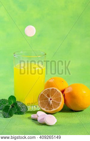 Fizzy Vitamin C Tablet Dissolves In A Glass Of Water And Fresh, Juicy Lemons. Concept Of A Vitamin S