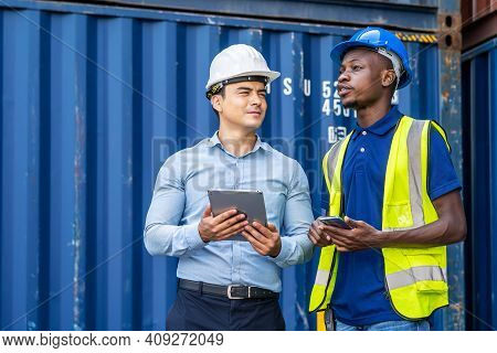 Port Manager And Engineer While Standing By Freight Containers On A Large Commercial Dock Discussing