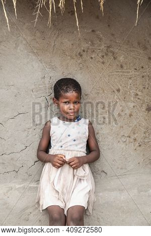 Small African village girl sitting on the edge of a cracked wall in her yard in Botswana