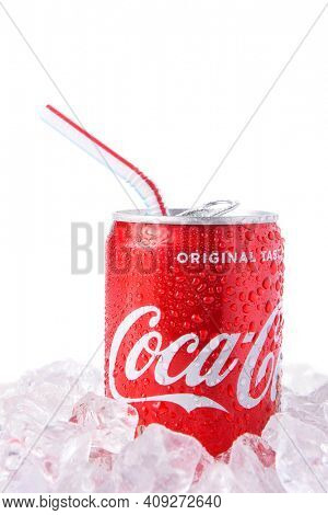 IRVINE, CALIFORNIA - MARCH 12, 2018: A can of Coca-Cola with drinking straw on ice. Coca-Cola is the one of the worlds favorite carbonated beverages.