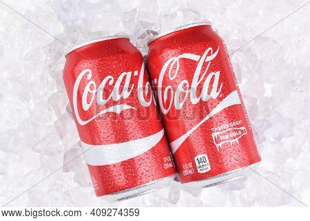 IRVINE, CALIFORNIA - JULY 10, 2017: Two Coca-Cola Cans on a bed of ice with condensation. Coke is the most popular carbonated soft drink in the world.