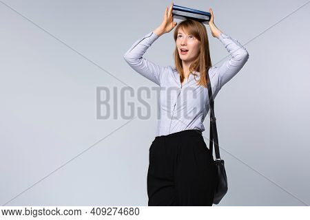 An Enthusiastic Student Holding Books With Both Hands Above Her Head Sees The Future And Success In
