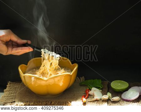 Instant Noodles With Hand Woman Clamping Instant Noodles From White Bowl On Black Background. Fast F