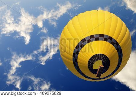 Yellow Hot Air Balloon On Blue Sunlight Sky With Clouds. Bottom View.