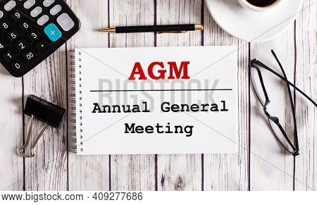 Agm Annual General Meeting Is Written In A White Notepad Near A Calculator, Coffee, Glasses And A Pe