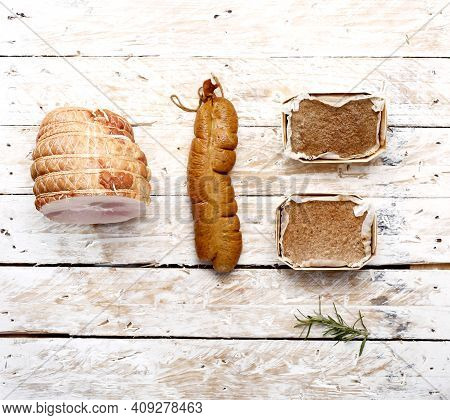 A Top View Of Pork Ham, Liver Sausage And Two Portions Of Pate In Baking Moulds, On Light Wooden Boa