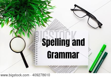 On A White Background Lies A Notebook With The Words Spelling And Grammar, Glasses, A Magnifying Gla
