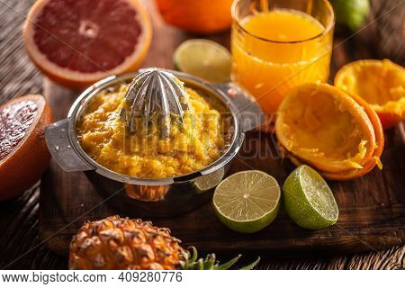 Squeezed Orange Pulp In A Juicer With Cfreshly Cut Citruses And A Glass Of Juice.