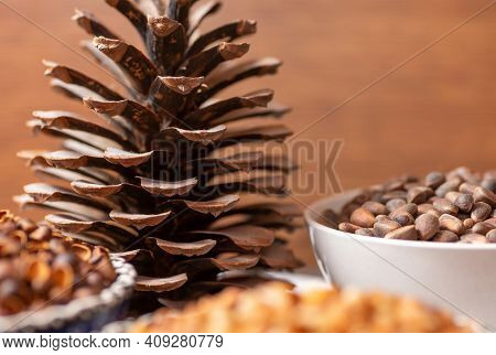 A Large Open Pine Cone Next To A Ceramic Bowl. They Contain Pine Nuts, Shells And Peeled Nuts. Close