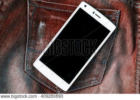 White Smartphone On Shabby Rusty Orange Frayed Jeans Background Hipster Modern Lifestyle Mock Up To