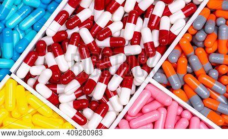 Top View Capsule Pills In Plastic Box. Multi Colored Capsule Pills. Vitamin And Supplement Concept.