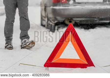 Warning Road Sign Triangle Close-up On The Background Of A Man's Legs, Car. Winter Travel, Road Prob