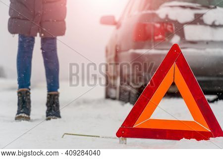 Warning Road Sign Triangle Close-up On The Background Of A Woman's Legs, Car. Winter Travel, Road Pr