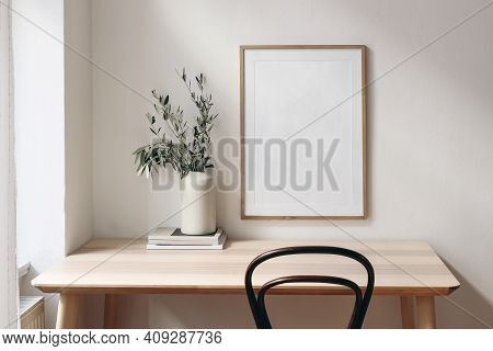 Home Office Concept. Old Books, Empty Vertical Wooden Picture Frame Mockup Hanging On White Wall. Wo