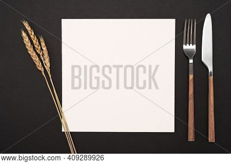 Mockup Blank Card And Cutlery On Black Table. Top View White Recipe Paper Page With Mockup Text Spac