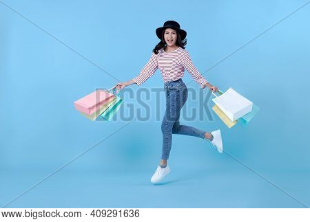Cheerful Happy Thai Asian Woman Enjoying Shopping,  She Is Carrying Shopping Bags And Jumping To Get