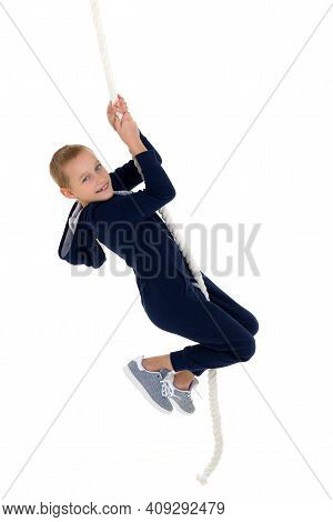 Active Smiling Boy Hanging On Swing Rope. Kid Playing And Having Fun Doing Activities. Happy Child W