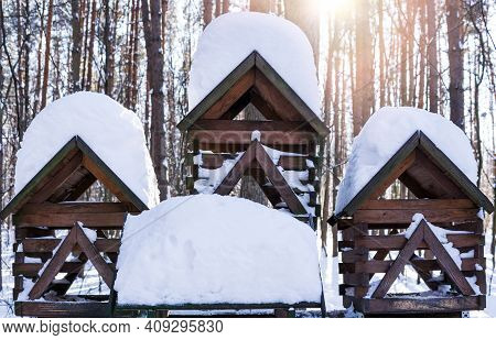 Wooden Bird Feeder In The Park With A Large Snowdrift On The Roof.