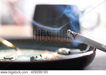A Smoking Cigarette In A Saucer. Smouldering Cigarette Butt For Depicting The Danger Of Fire, Lung D