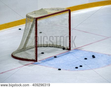 Hockey Gates On Ice Close-up. Several Pucks Are Visible Near The Goal And Behind The Net. The Pucks