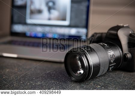 Professional Camera On A Blurred Background With A Laptop. The Concept Of Working With Photos And Vi