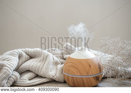 Aroma Composition With A Modern Aroma Oil Diffuser On A Wooden Surface With A Knitted Element And A
